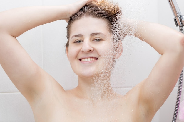 Donna allegra in piedi alla doccia e lavando la testa