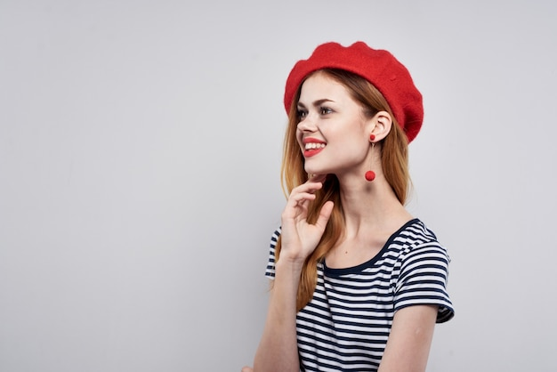 La donna allegra in una maglietta a strisce delle labbra rosse fa un gesto con le sue mani isolate sullo sfondo