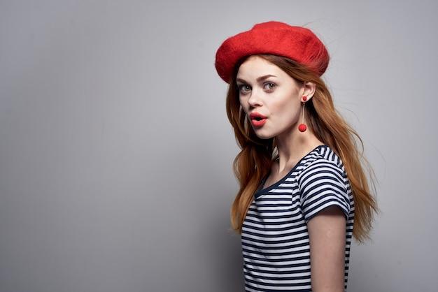 Donna allegra in un gesto di labbra rosse maglietta a righe con le sue mani estate