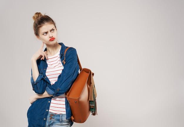 Studentessa allegra con moda zaino in posa sfondo chiaro