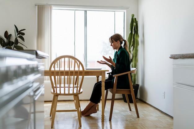 Donna allegra in una videochiamata mentre lavora da casa durante la pandemia di coronavirus