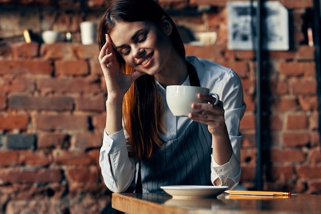 Cameriere donna allegra con una tazza di caffè in un bar che lavora