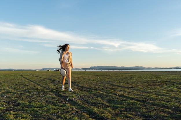 La donna allegra cammina attraverso il campo verde con la luce del sole