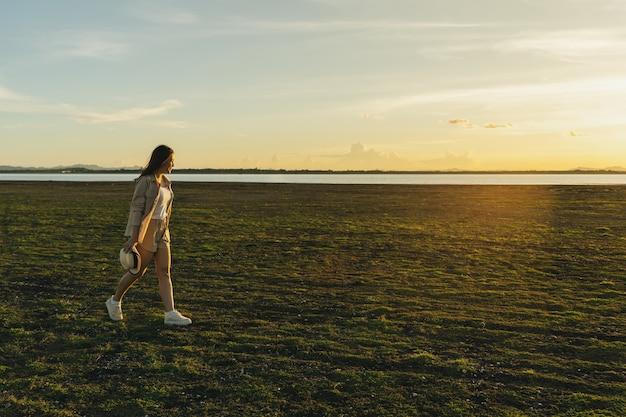 La donna allegra cammina attraverso il campo verde con il tramonto