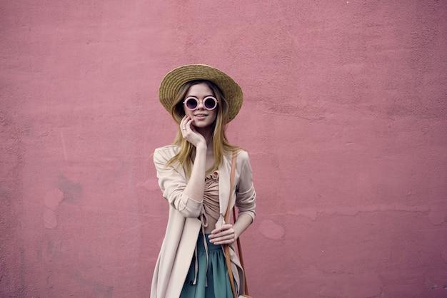 Donna allegra a piedi all'aperto in stile elegante contro il fondo della parete. foto di alta qualità