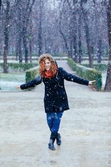 Donna allegra che cammina sotto la neve