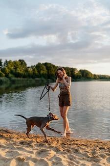 Donna allegra cammina con il suo cane weimaraner in riva al lago