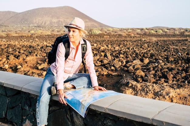 Donna allegra vagabondo con un look alla moda che cerca la direzione sulla mappa della posizione mentre si viaggia all'estero in estate, felice turista femminile alla ricerca del prossimo posto da visitare nella montagna del deserto del paese vacati