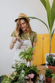 Donna allegra che innaffia le sue piante d'appartamento
