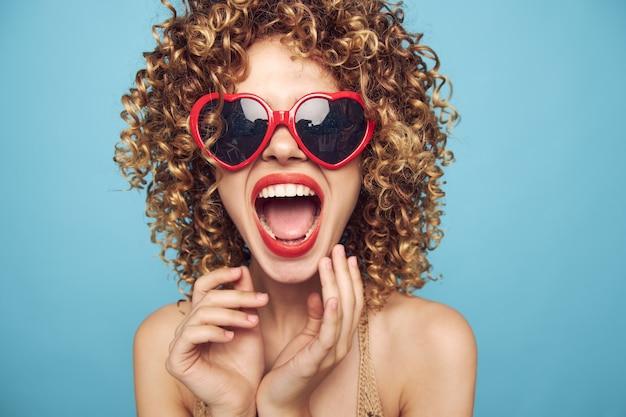 Donna allegra indossando occhiali scuri labbra rosse bocca aperta guardare avanti spalle nude parete blu
