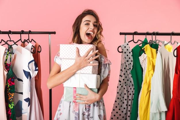 Donna allegra che indossa un abito in piedi in negozio vicino appendiabiti con scatole presenti isolato sul rosa
