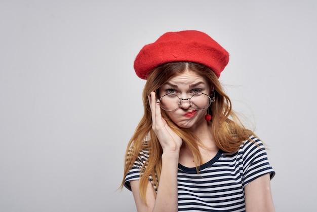 Donna allegra che indossa occhiali in posa moda aspetto attraente orecchini rossi gioielli aria fresca