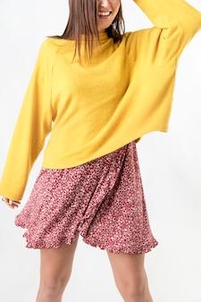 Donna allegra che indossa un maglione giallo senape su un vestito a fiori rossi
