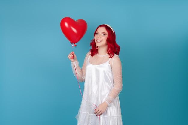Donna allegra in un abito bianco con i capelli rossi tiene in mano un palloncino volante a forma di cuore