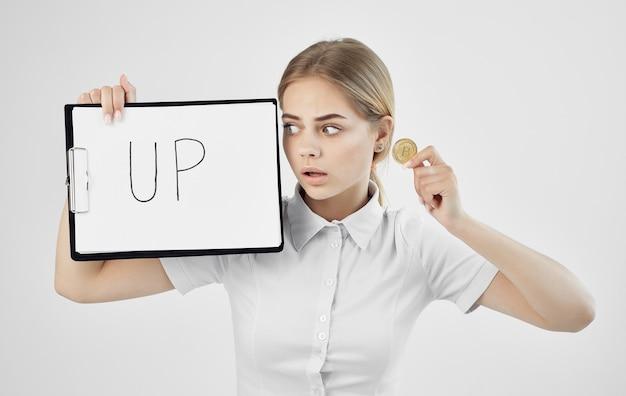 La donna allegra in una camicia bianca tiene una cartella con l'iscrizione verso l'alto criptovaluta bitcoin internet finlandia