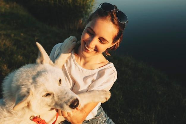 Donna allegra in camicia bianca e occhiali da sole che abbraccia grande cane bianco che si siede insieme con gli occhi chiusi alla fonte d'acqua