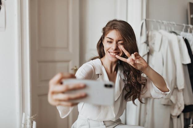 Donna allegra in camicia bianca che fa l'occhiolino, mostra il segno della pace e si fa selfie