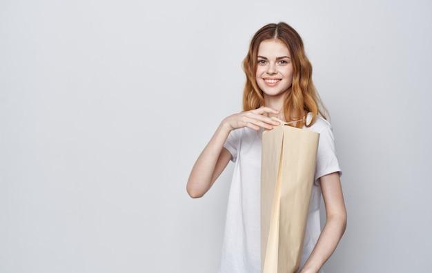 Donna allegra in una maglietta bianca con un pacchetto nelle sue mani shopping