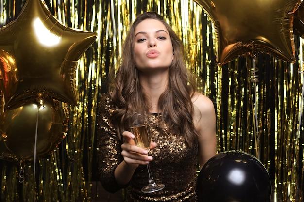 Donna allegra con palloncini che ridono su fondo oro.