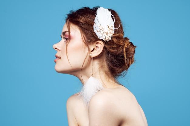 Donna allegra con le spalle nude trucco luminoso orecchini soffici sfondo blu
