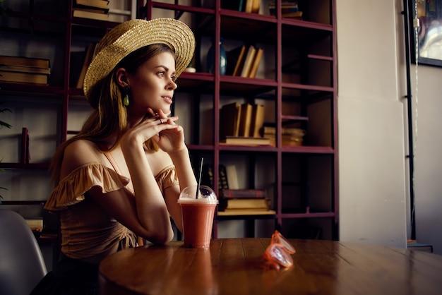 Donna allegra con un libro nelle mani di un caffè fashion