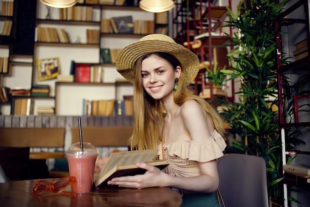 Donna allegra con un libro nelle mani di uno stile di vita da caffè