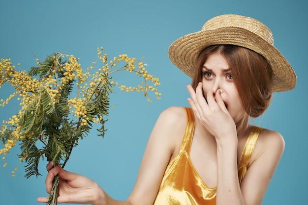 Donna allegra con un mazzo di fiori in un cappello di mimosa sfondo blu