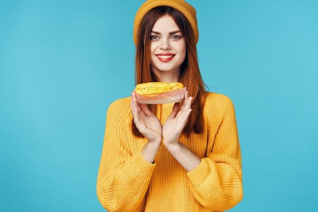 Donna allegra con una tazza di bevanda calda e cupcake nello stile di vita della colazione delle mani
