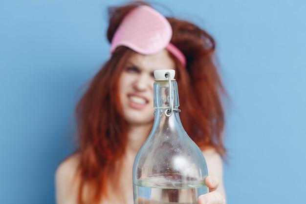 Donna allegra con i capelli arruffati e una bottiglia di maschera di sonno vacanza alcolica
