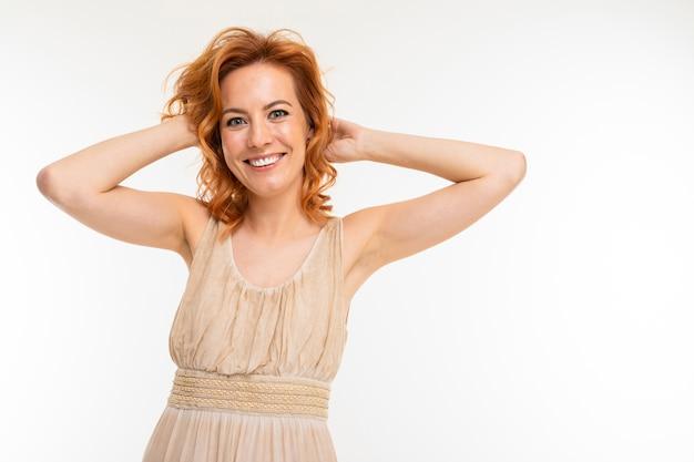 Donna allegra con capelli rossi biondi in un bel vestito sorride, foto isolato su sfondo bianco