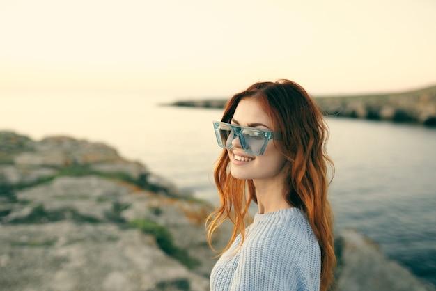 Donna allegra con gli occhiali all'aperto paesaggio viaggio dell'isola