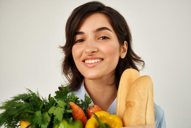 Donna allegra con un pacchetto di generi alimentari verdure consegna cibo sano