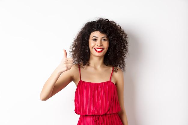 Donna allegra con labbra rosse e abito elegante, mostrando il pollice in alto e sorridente, consigliando il prodotto, in piedi su sfondo bianco.