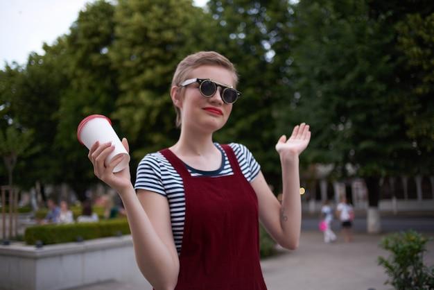 Donna allegra con i capelli corti all'aperto bicchiere con drink