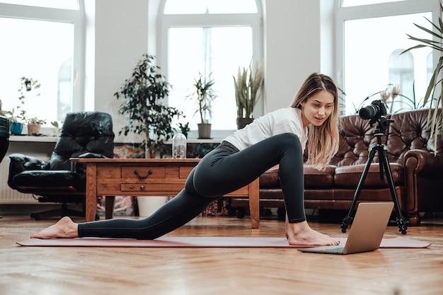 Istruttore di yoga allegro con laptop che mostra una certa postura sul pavimento in soggiorno con un design in stile.