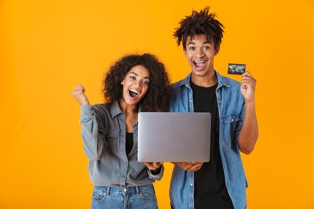 Allegro giovane coppia africana in piedi isolato, tenendo il computer portatile, celebrando, mostrando la carta di credito in plastica
