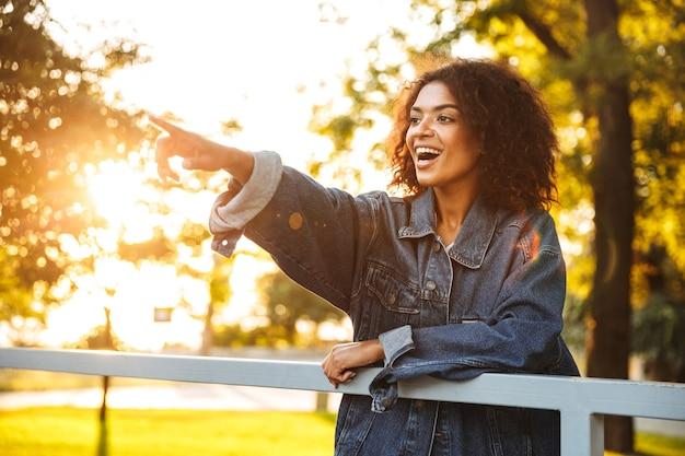 Allegro giovane ragazza africana in giacca di jeans
