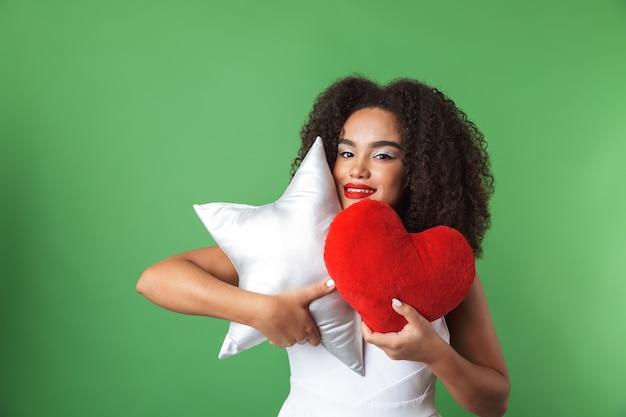 Allegro giovane donna africana che indossa un abito in piedi isolato, con cuscini a forma di stella ea forma di cuore