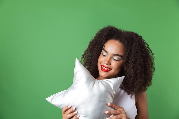 Allegro giovane donna africana che indossa un abito in piedi isolato, tenendo a forma di stella cuscino