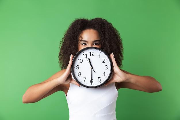 Allegro giovane donna africana che indossa abiti in piedi isolato, mostrando orologio da parete