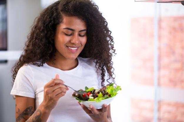 Allegra giovane donna afro-americana che mangia insalata di verdure nella cucina domestica - imagem.