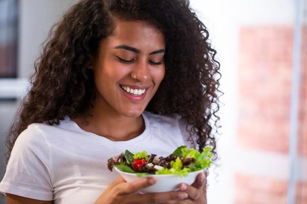 Allegra giovane donna afro americana che mangia insalata di verdure nella cucina di casa