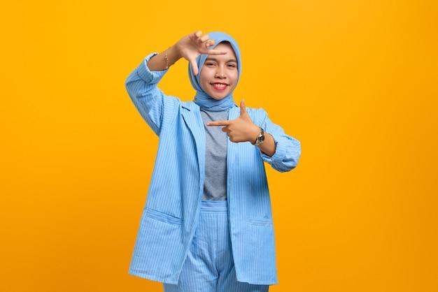 Allegra giovane donna asiatica che fa cornice con le mani e le dita isolate su sfondo giallo