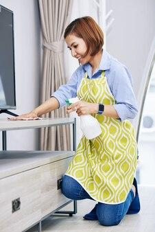 Allegra giovane donna asiatica che indossa il grembiule quando si puliscono le superfici in camera con spray disinfettante