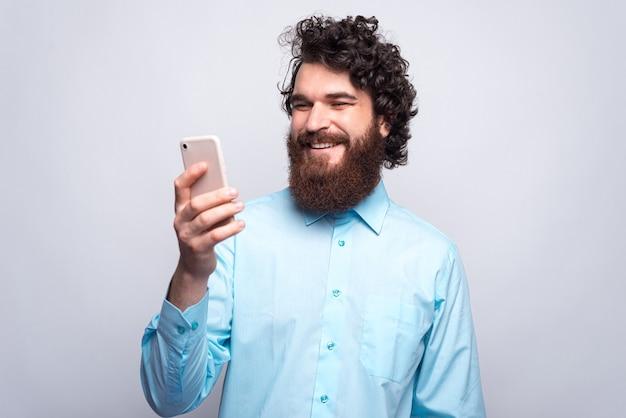 Allegro giovane barbuto hipster uomo in camicia blu utilizzando il suo smartphone e sorridente