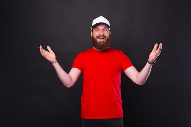 Allegro giovane barbuto in maglietta rossa che fa gesto di benvenuto