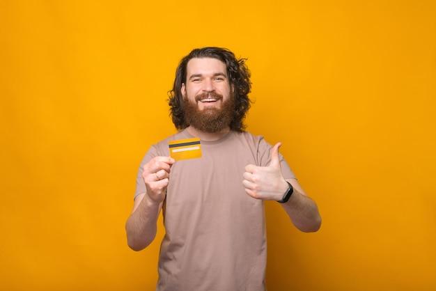 Allegro giovane uomo barbuto che mostra pollice in alto e la sua nuova carta di debito su giallo