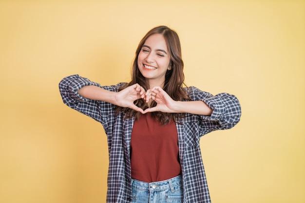 La giovane e bella ragazza allegra sta gesticolando un cuore con le dita