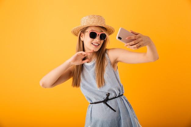 Allegro giovane donna bionda in cappello estivo