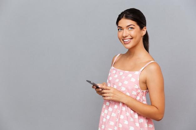 Giovane donna castana allegra in vestito rosa che tiene telefono cellulare isolato su un muro grigio